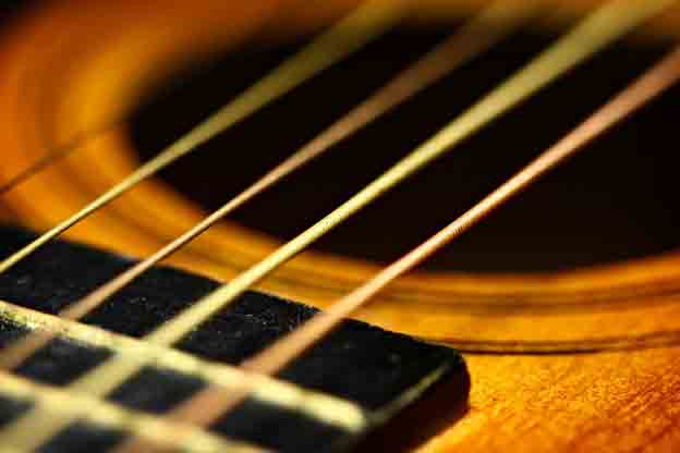 Closeup of strings on old guitar.